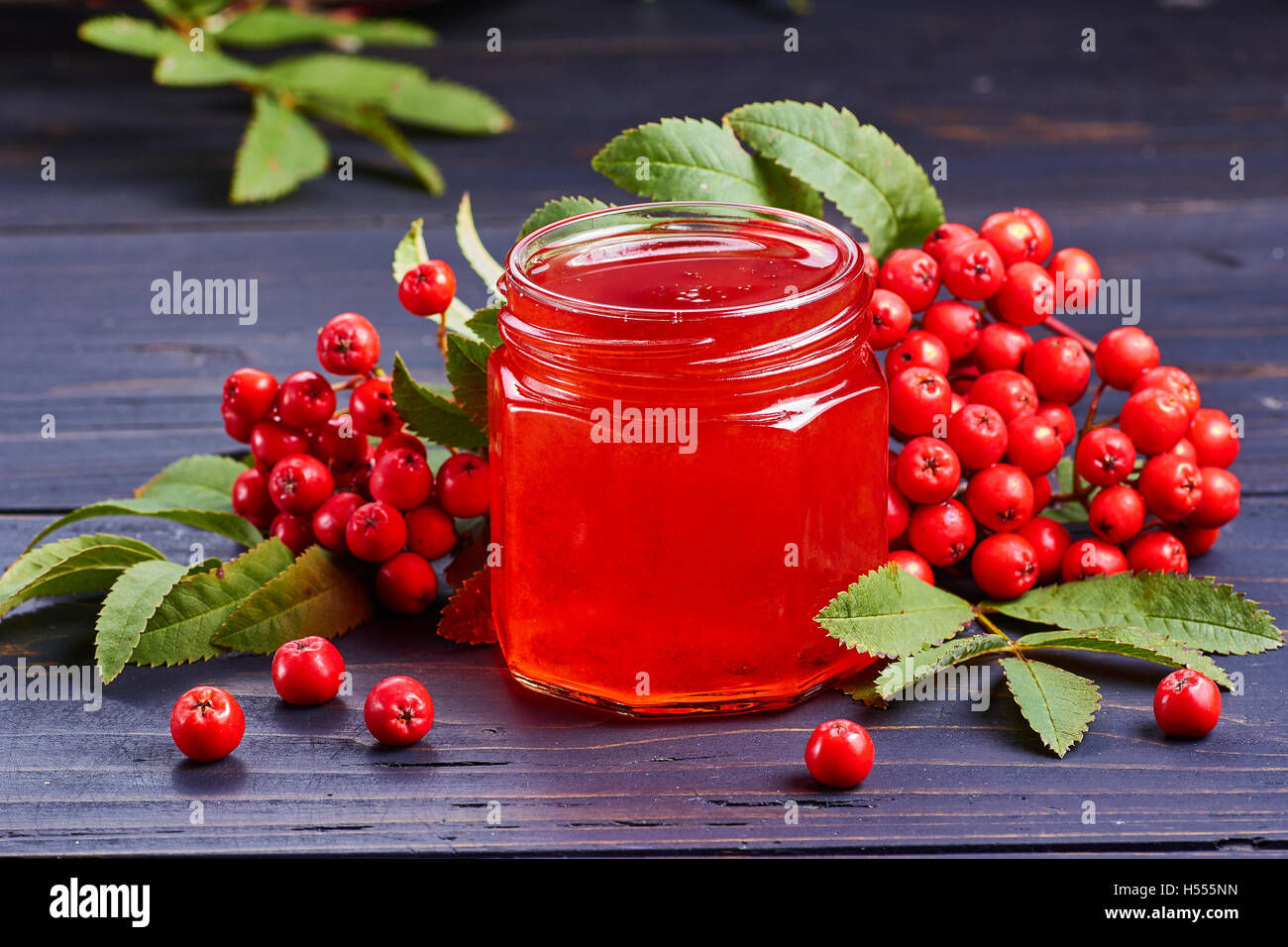 Glass jar with syrup of rowan berries on dark wooden table. - Stock Image