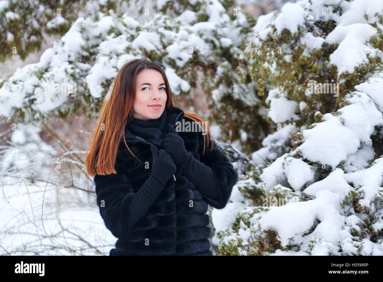 Sweet attractive girl in a fur coat and gloves in the winter park