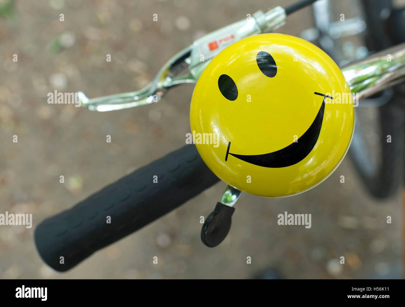 Bicycle handlebars with bell with laughing smiley - Stock Image