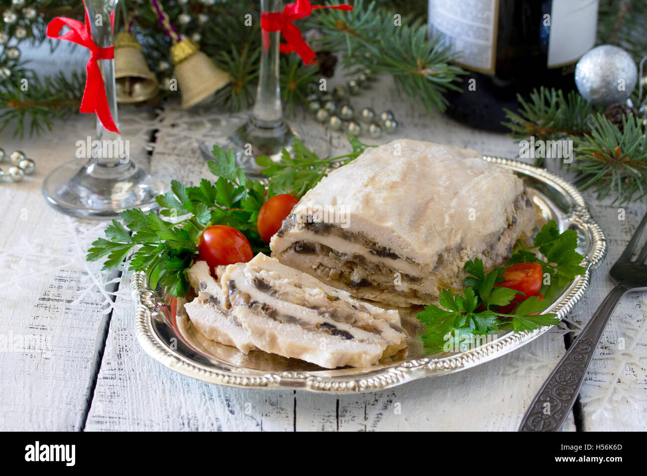 Homemade meat chicken roll with mushrooms, onions and gelatin on the Christmas table. - Stock Image