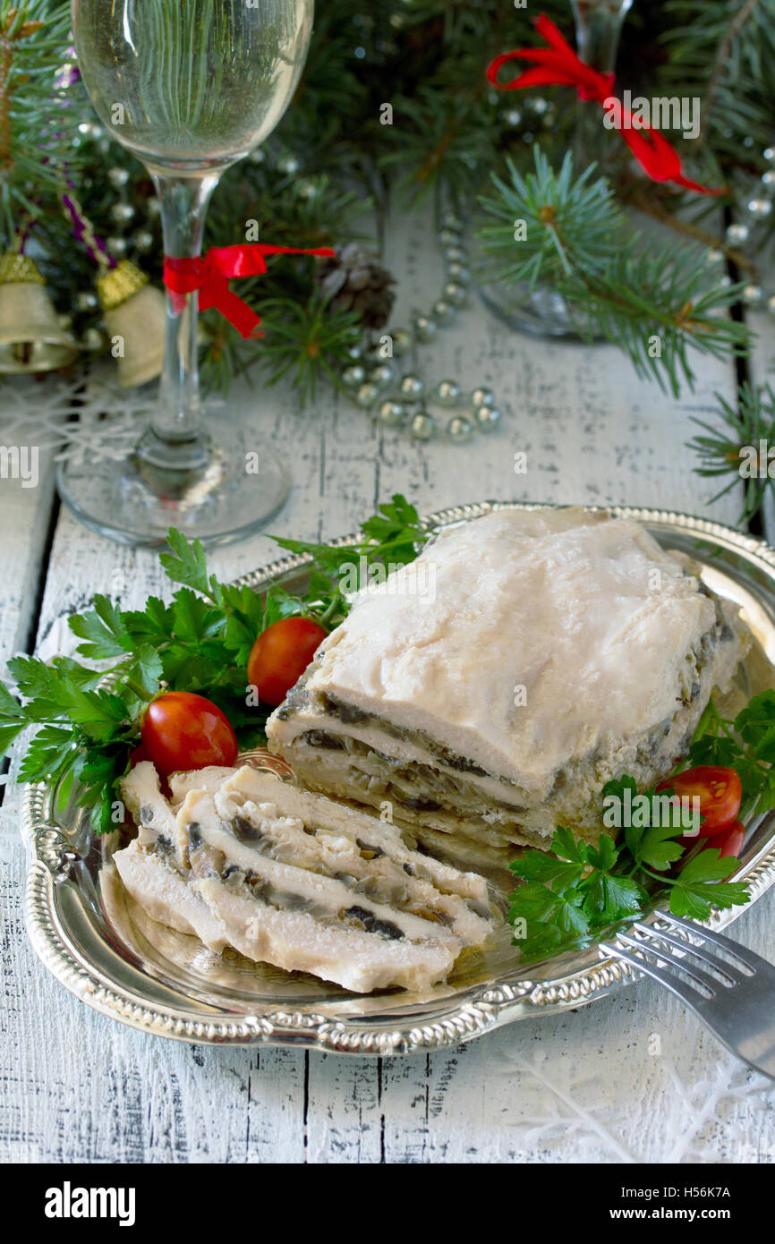 Homemade meat chicken roll with mushrooms, onions and gelatin on the Christmas table. Stock Photo