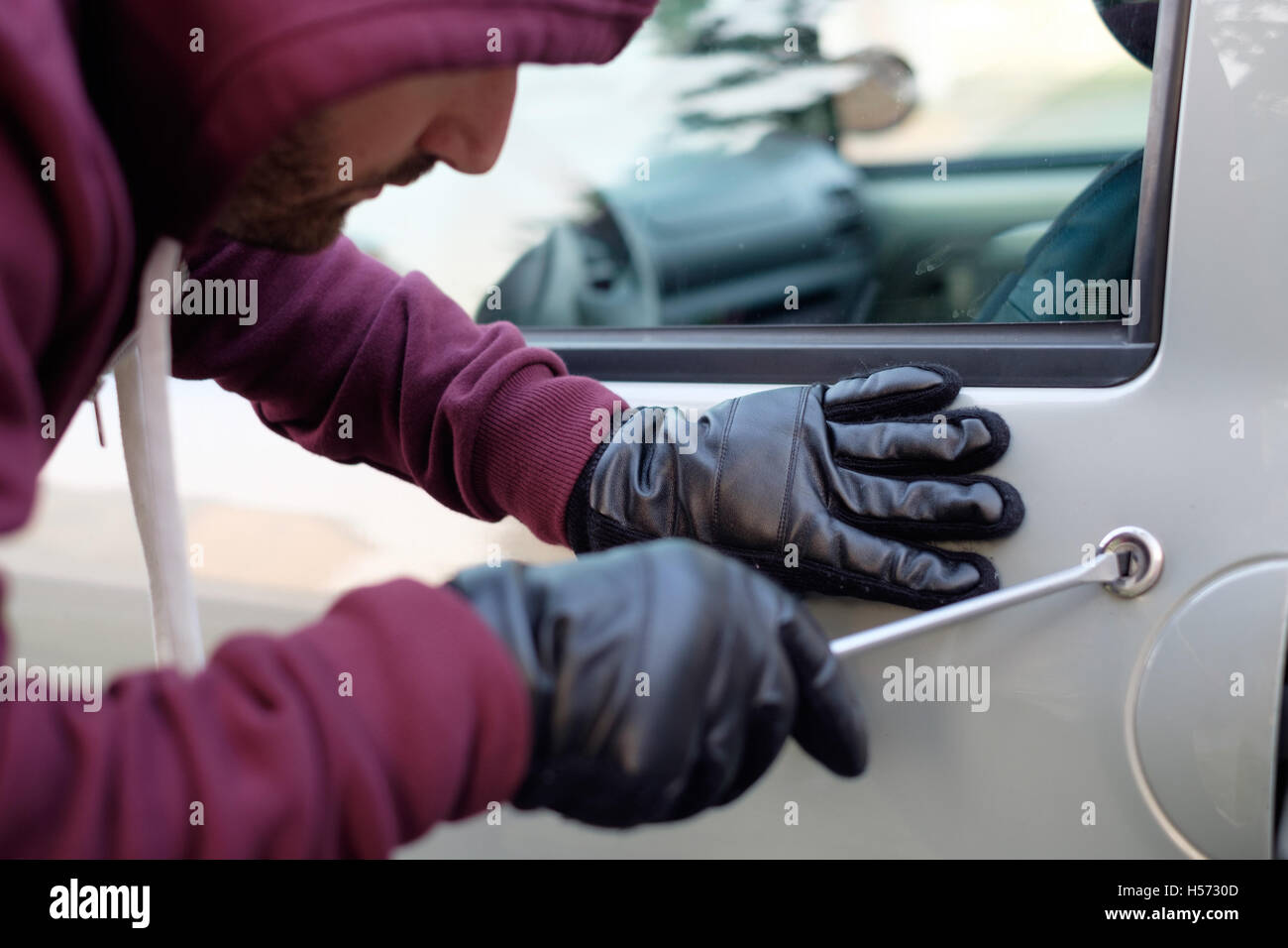 Hooded thief trying to open a car door lock - Stock Image