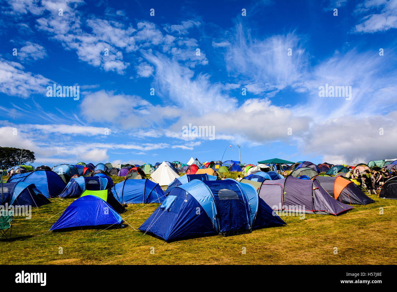 A collection of brightly coloured tents camping at Festival No.6, Portmeirion, Wales, UK - Stock Image
