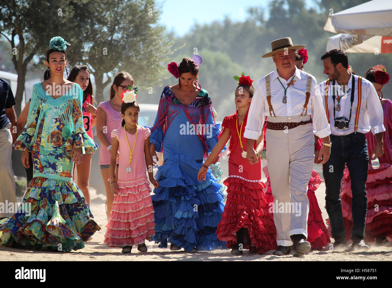 HUELVA/SPAIN - 9 OCTOBER 2016: Piligrims in colorful dresses going to the sunday holy mass at the shrine of El Rocio - Stock Image