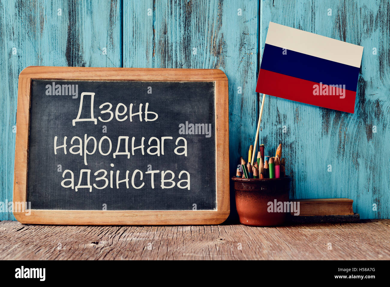 a chalkboard with the text National Unity Day written in Russian, a pot with pencils, some books and the flag of - Stock Image