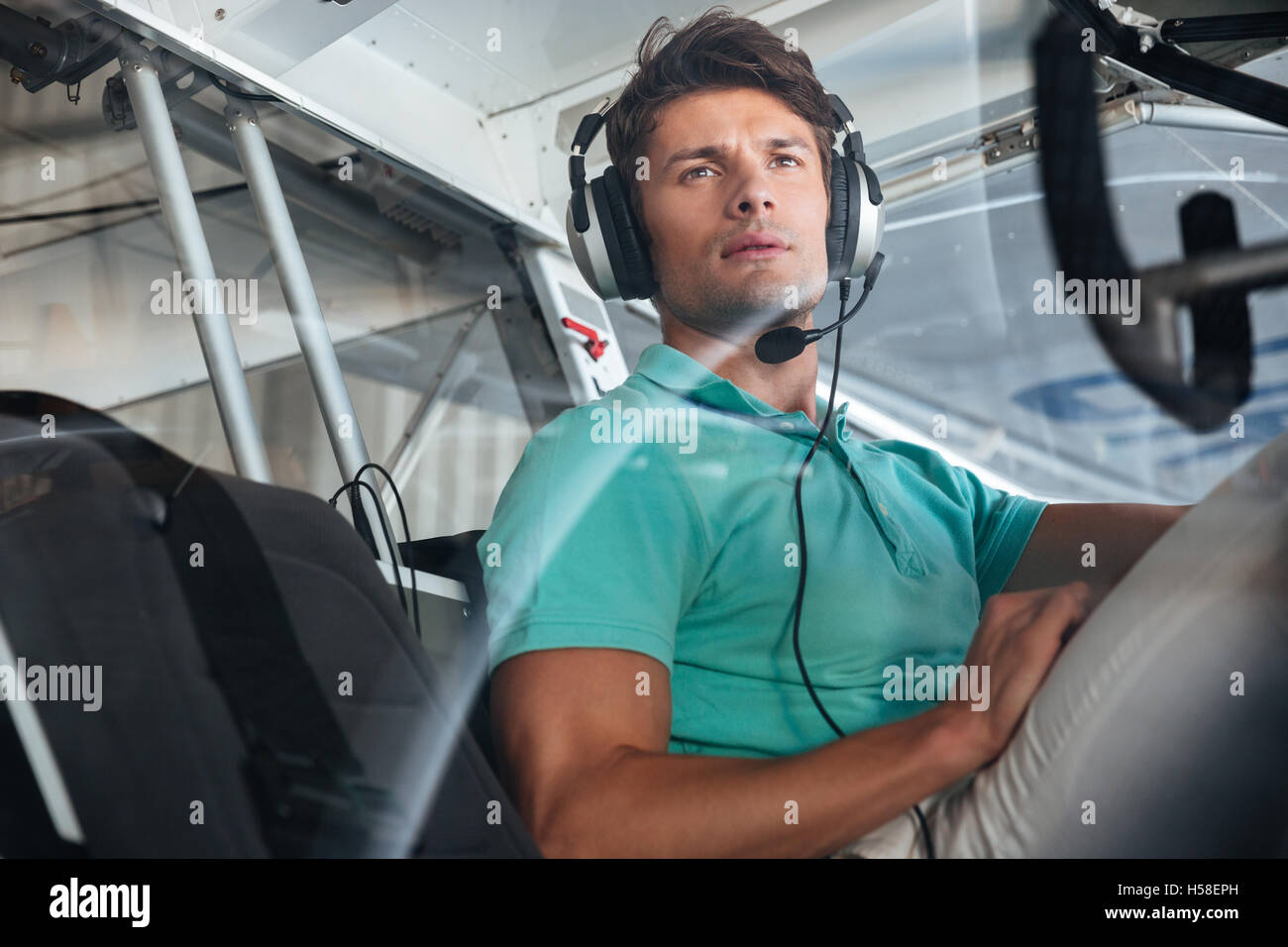 Portrait of serious young man pilot in cabin of private aircraft - Stock Image