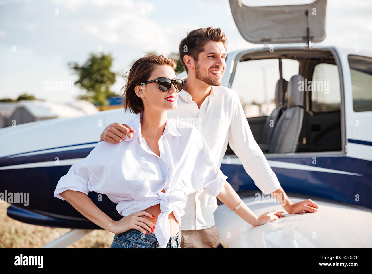 Portrait of beautiful young couple standing near small private aircraft - Stock Image