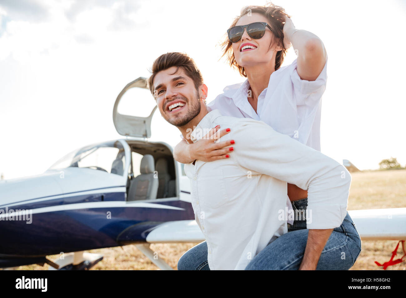 73ccfc72a8a Happy young couple laughing and having fun on runway near private aircraft  - Stock Image