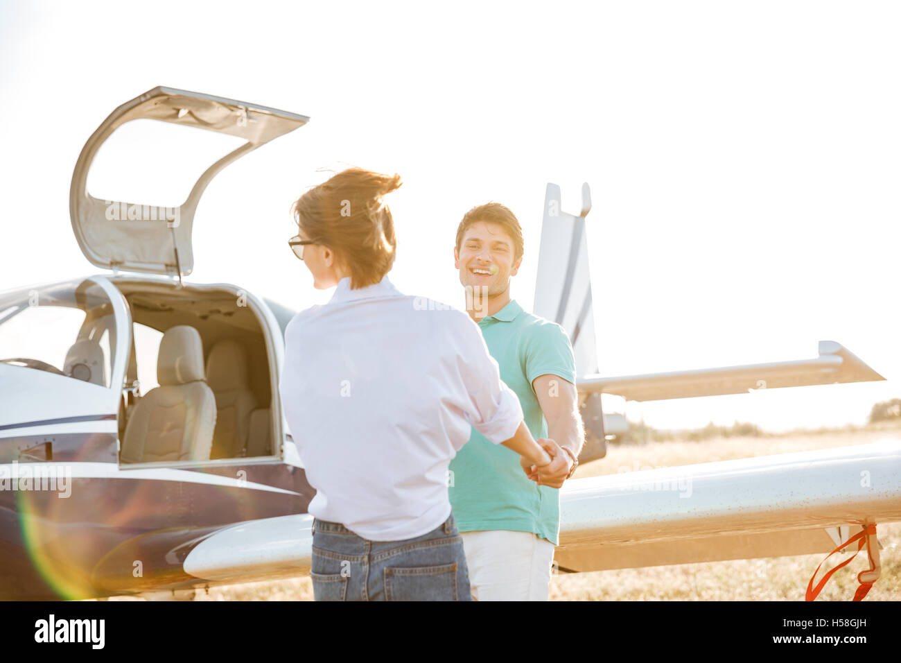Happy young couple holding hands and having fun on runway near private aircraft - Stock Image
