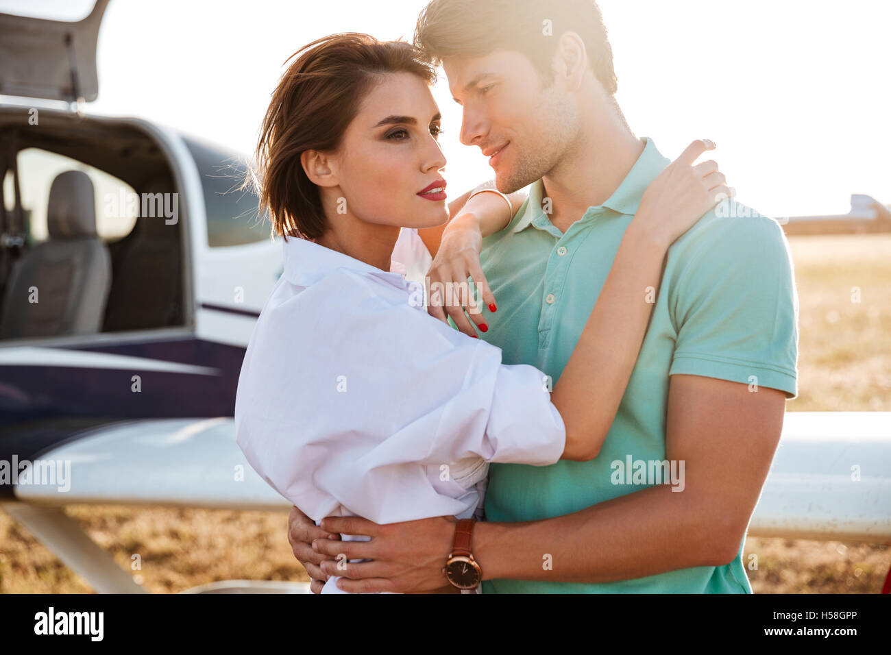 Beautiful young couple standing and hugging near private aircraft - Stock Image
