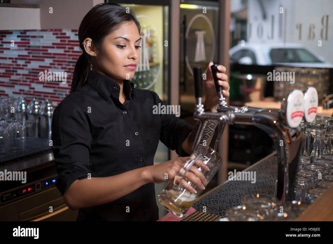 Female bartender pouring a draft beer. - Stock Image