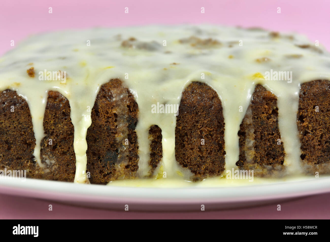 Home made carrot cake with icing against a pink background - Stock Image