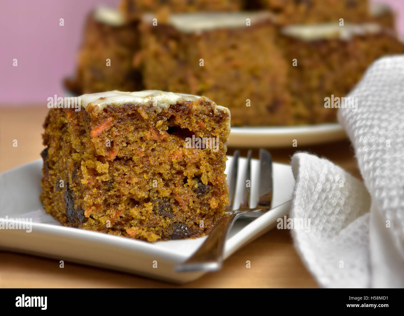 Home made carrot cake close up with out of focus cake in background - Stock Image