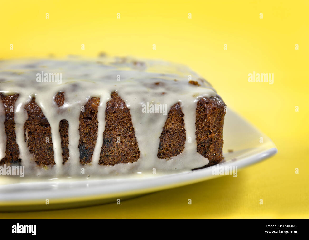 Home made carrot cake with icing against a yellow background - Stock Image