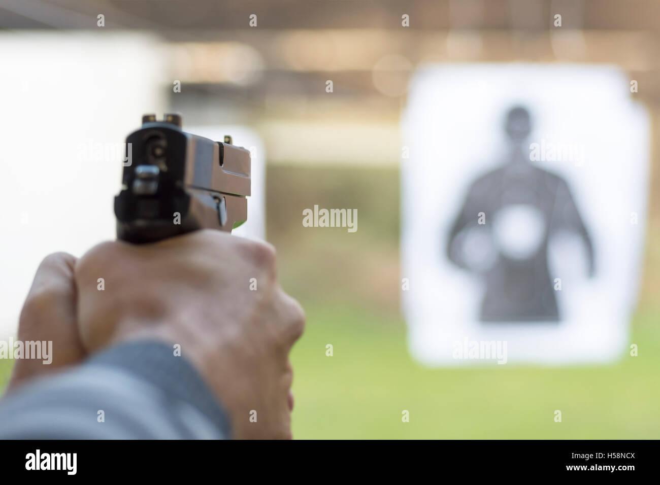 Man Firing Pistol at Target in Shooting Range - Stock Image