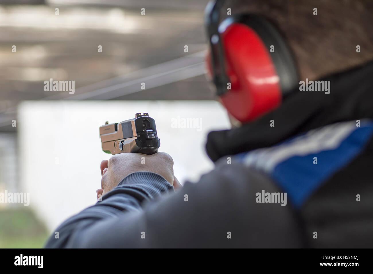 Shooting with Gun at Target in Shooting Range. Man Practicing Fire Pistol Shooting. - Stock Image