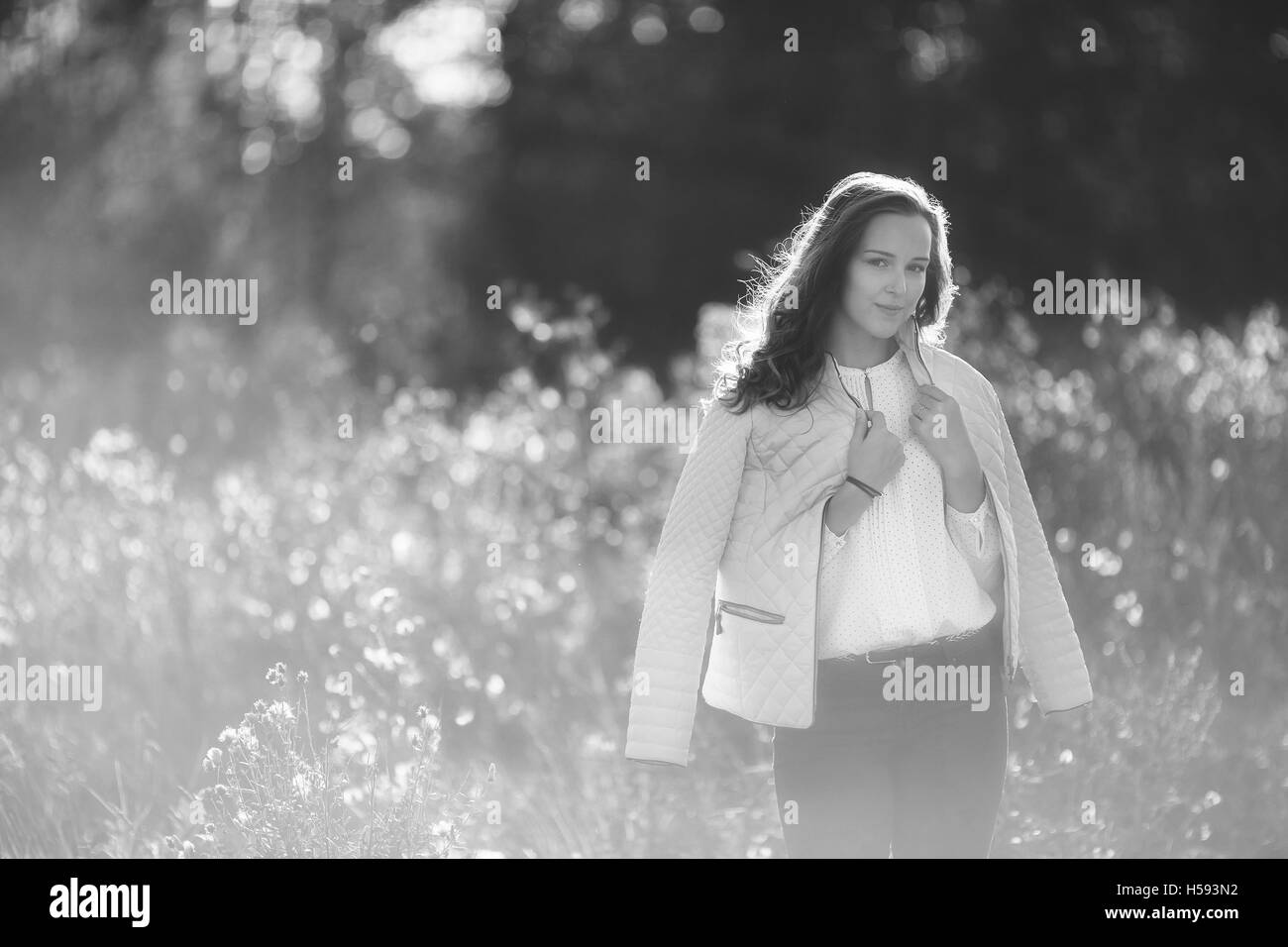 Black and white photo of attractive girl in park, bw - Stock Image