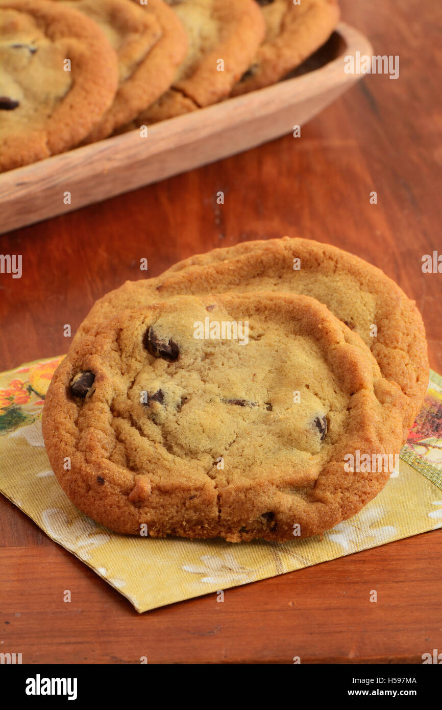 Fresh baked chocolate chip cookies on napkin with wooden tray of cookies in background in vertical  format.  Shallow - Stock Image