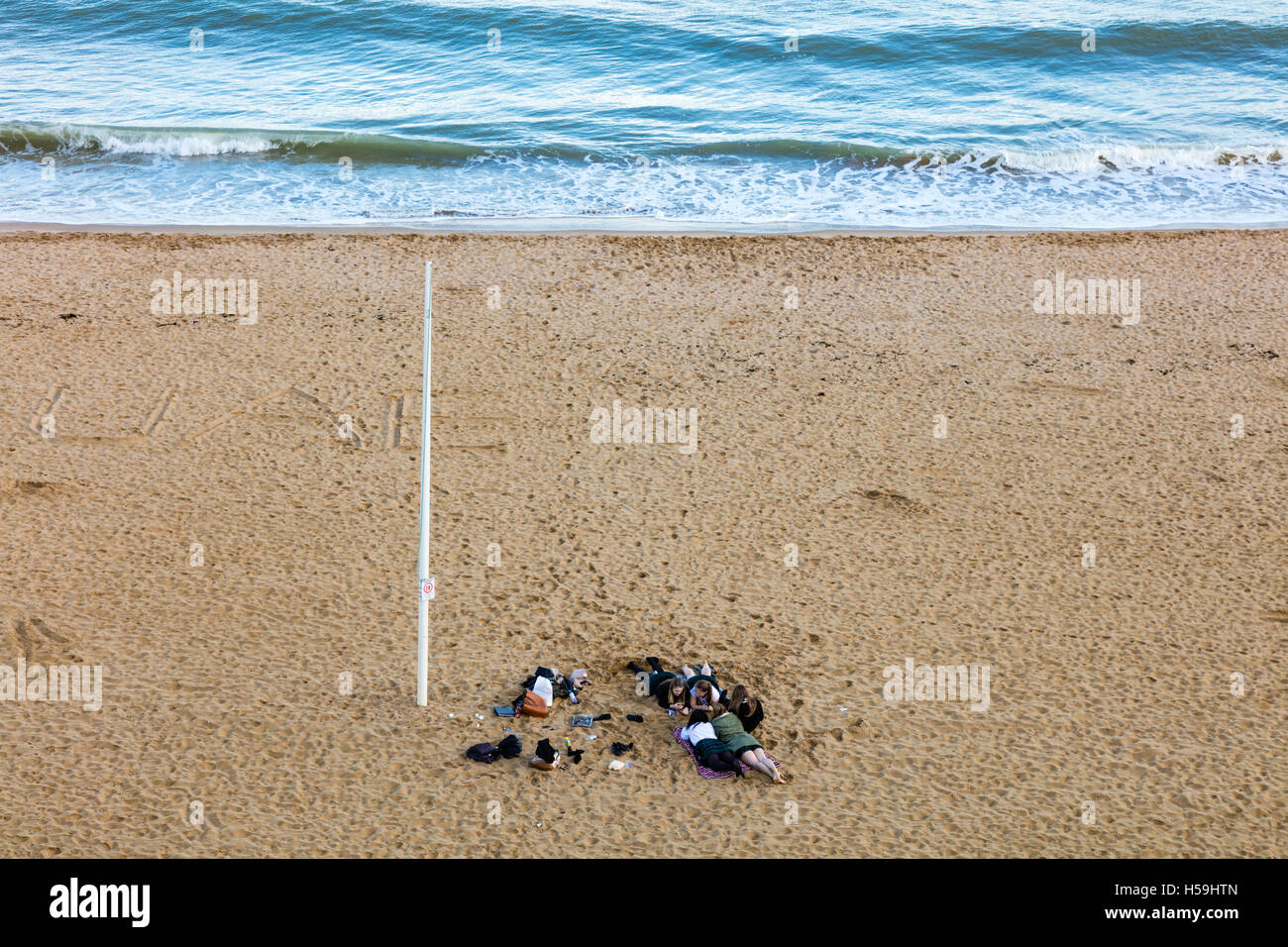 A group of schoolgirls lie on a sandy beach at Broadstairs, after school, Kent, UK - Stock Image