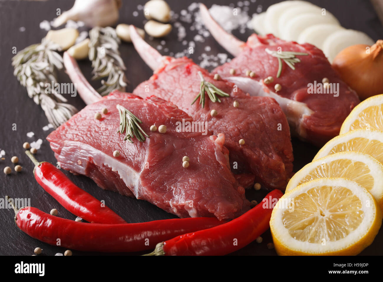Raw beef steak with spices on a black stone table closeup. horizontal Stock Photo