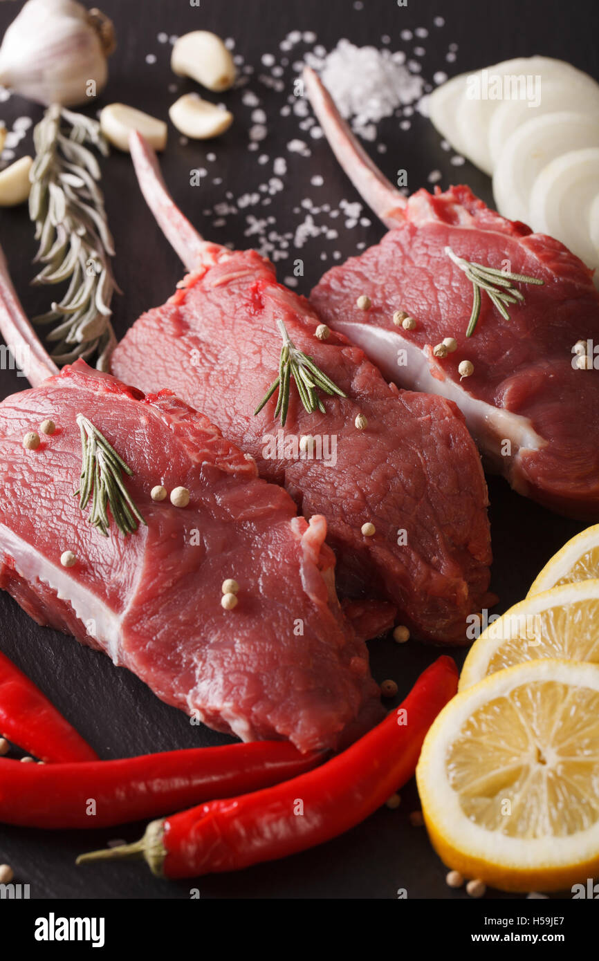 Raw beef meat with spices on a slate blackboard closeup. vertical - Stock Image