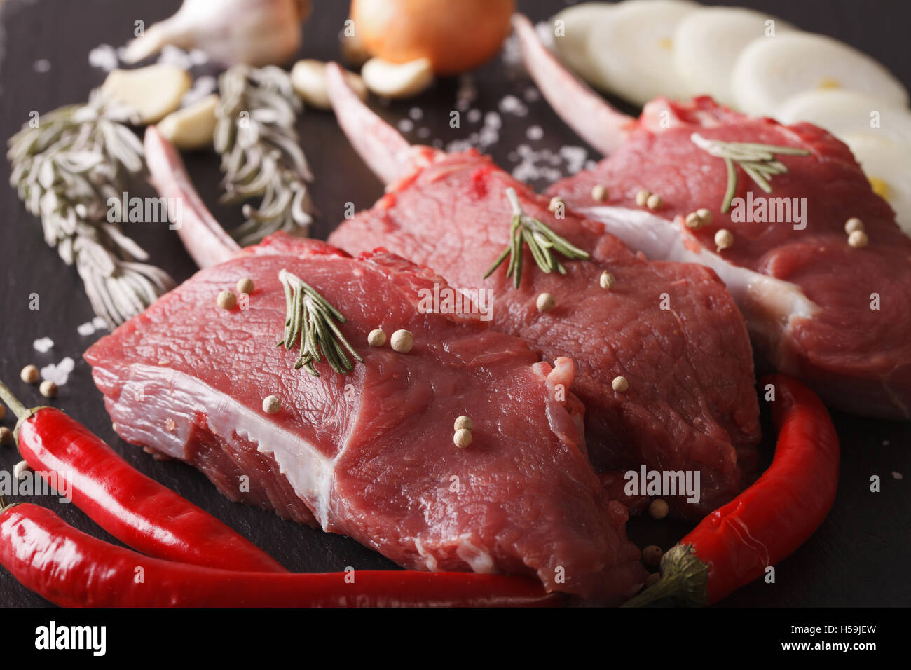 Raw beef steaks with rosemary on a slate table macro. Horizontal Stock Photo
