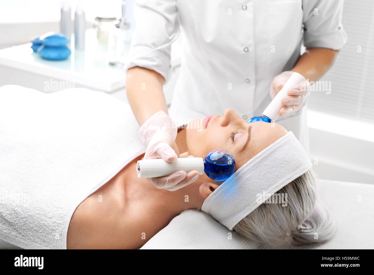 Cosmetic treatment, facial massage glass balls Masseuse, beautician performs a facial massage with glass balls. Stock Photo