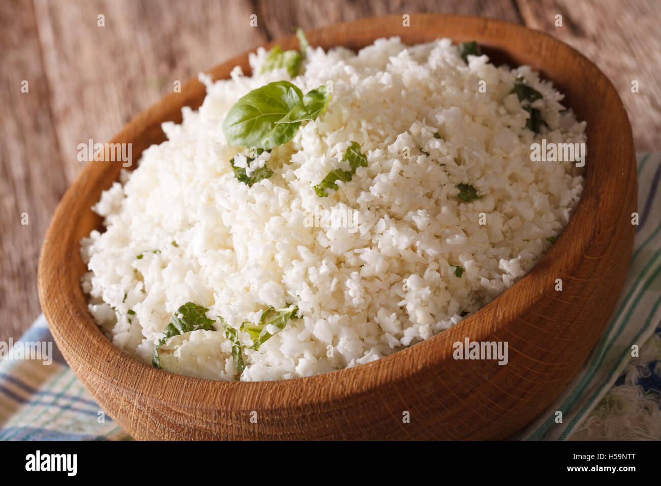 Cauliflower rice with basil close up in a bowl on the table. horizontal - Stock Image