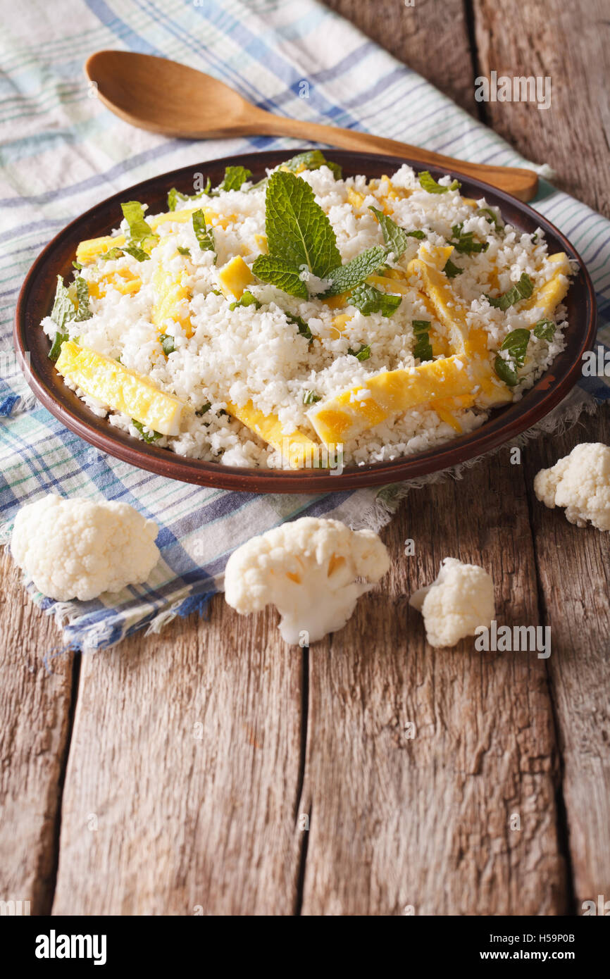 Dietary food: cauliflower rice with scrambled eggs and herbs closeup on a plate. Vertical Stock Photo
