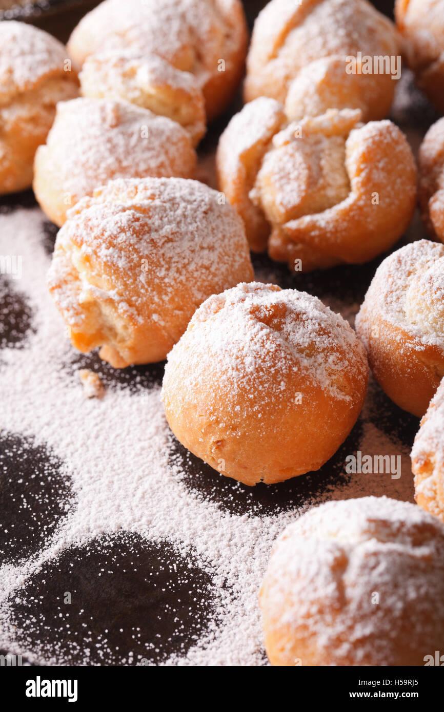 Italian street food: fried donuts Castagnole macro on a black plate. Vertical - Stock Image