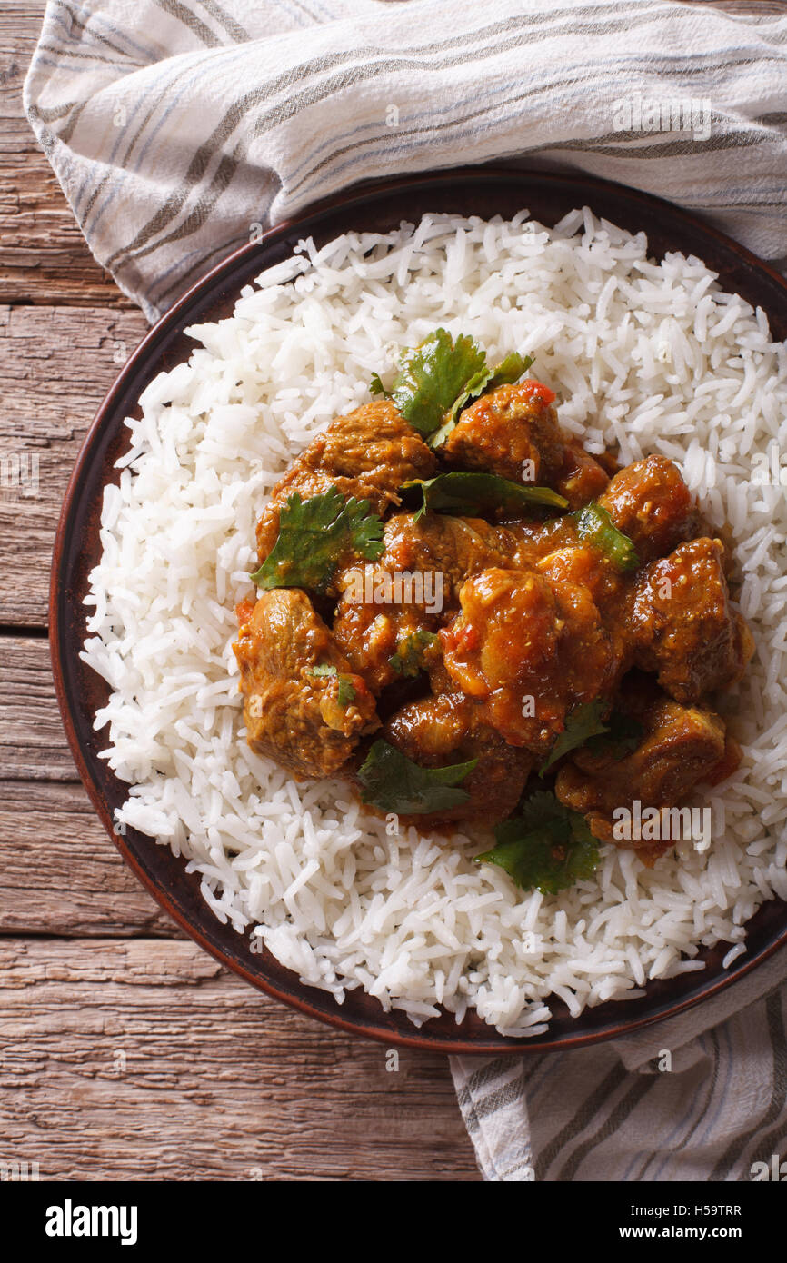 Indian food: Madras beef with basmati rice on the table close-up. vertical view from above - Stock Image
