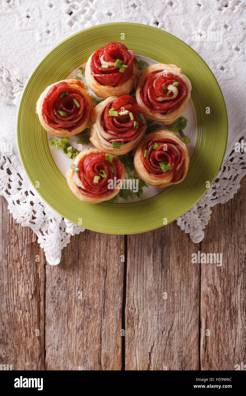 Baked rolls with salami in the form of roses on the table. Vertical top view - Stock Image