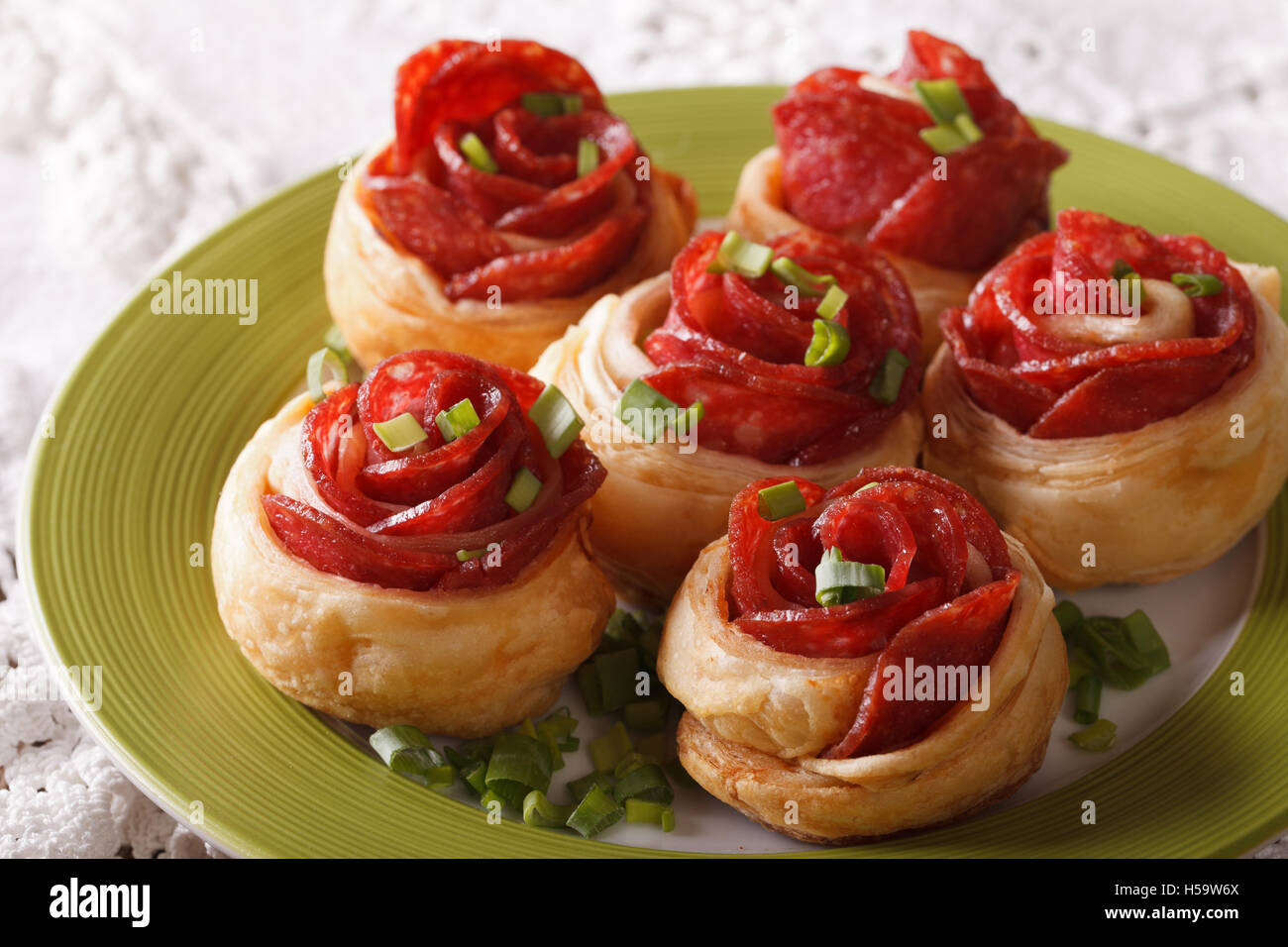 baked roll with salami and cheese in the form of roses close-up on a plate. horizontal - Stock Image