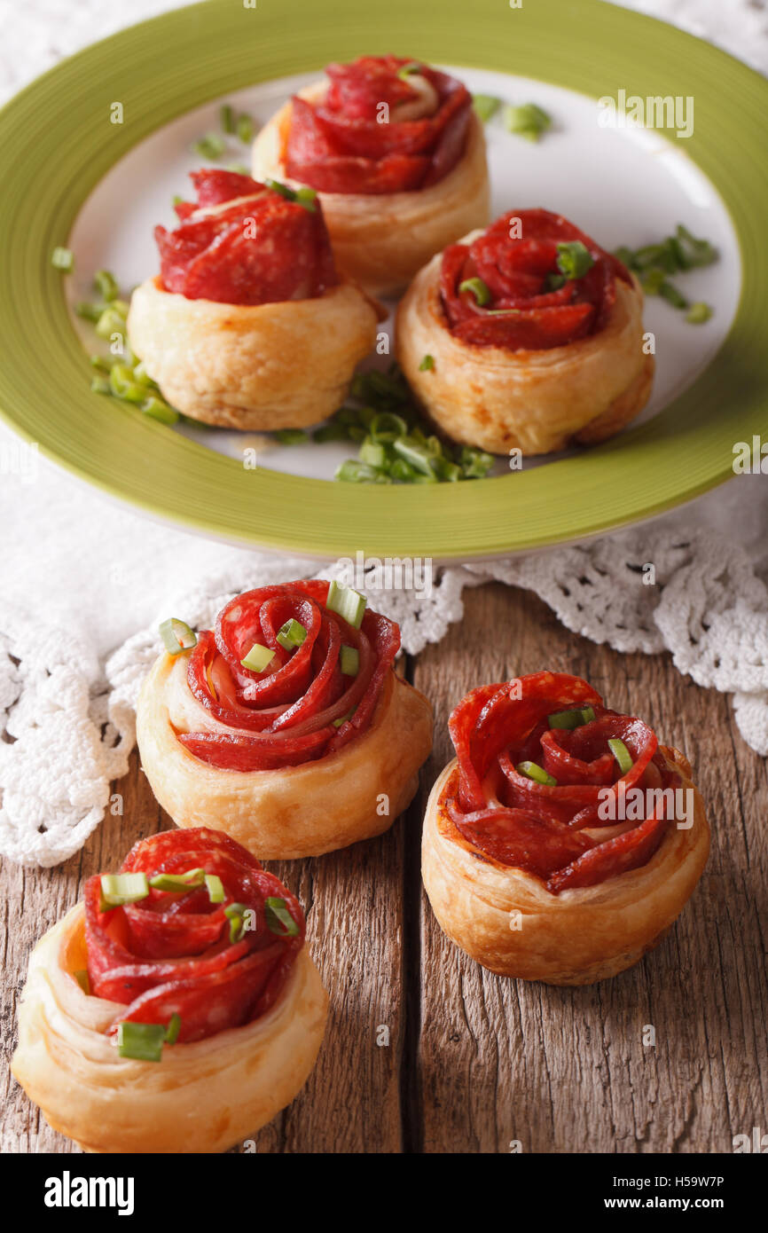 Baked rolls with salami in the form of roses on the table. vertical - Stock Image