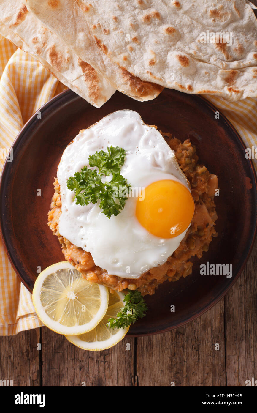 Egyptian breakfast: ful medames with a fried egg and bread close-up on the table. vertical view from above - Stock Image