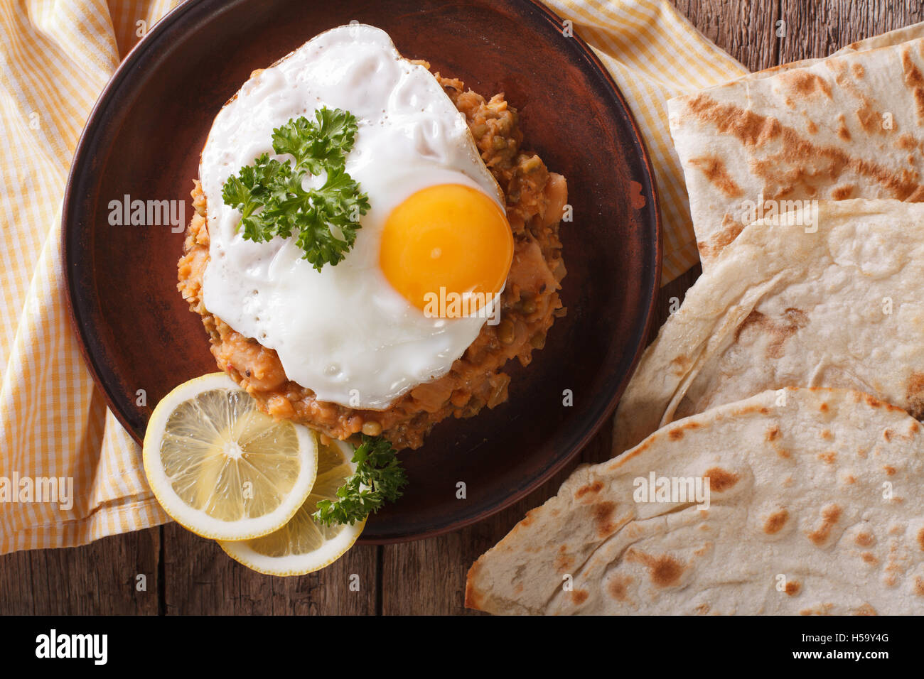ful medames with a fried egg and bread close-up on the table. Horizontal view from above - Stock Image