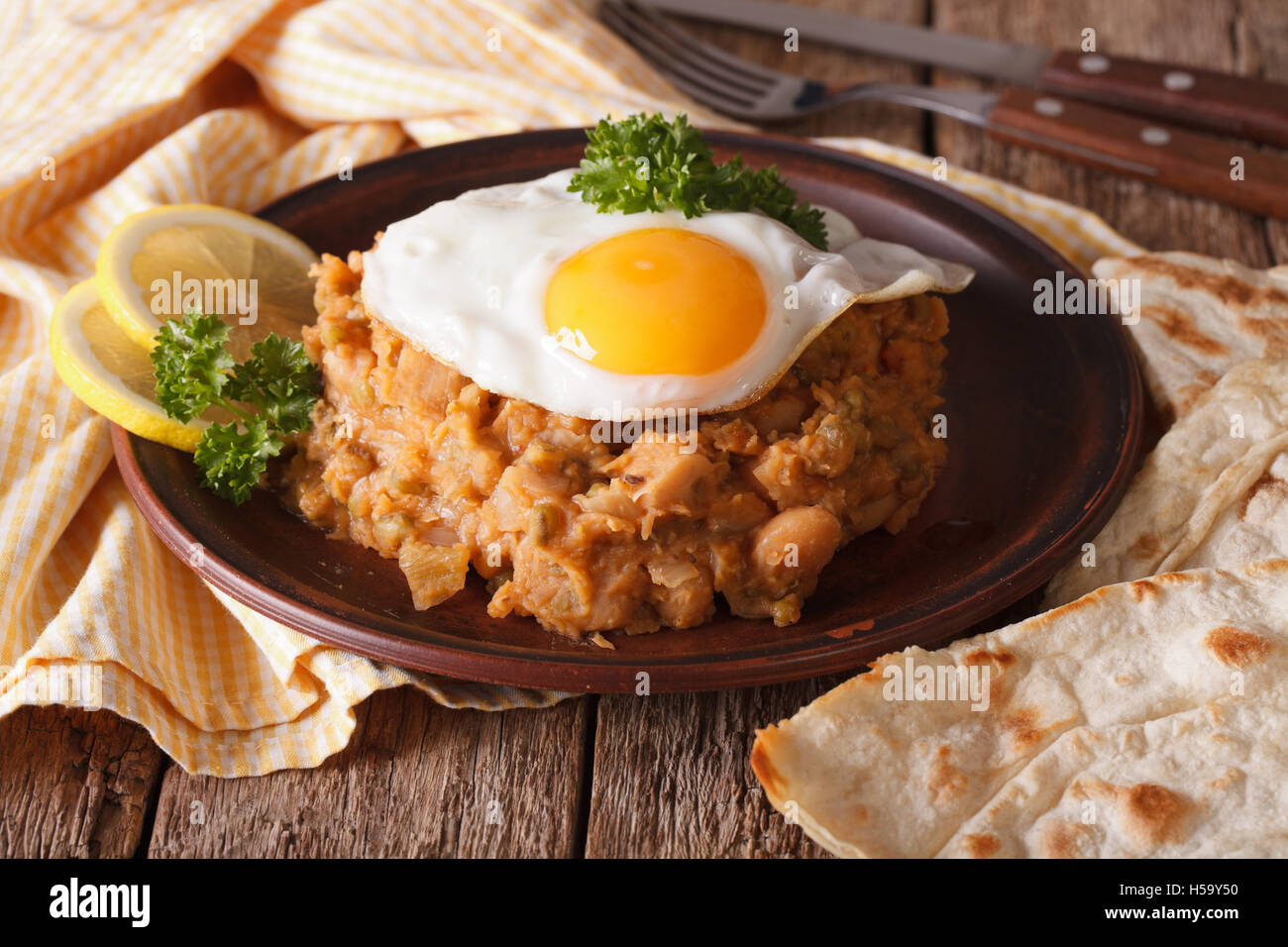 Arabic ful medames with a fried egg and bread close-up on the table. horizontal - Stock Image