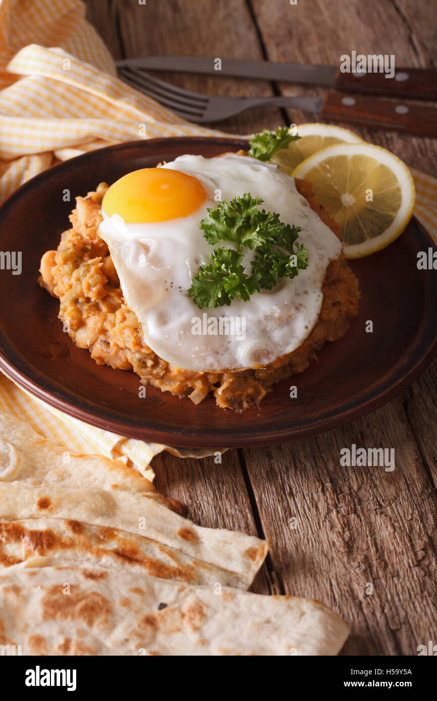 Arabic Breakfast: ful medames with a fried egg on a plate close-up. Vertical - Stock Image