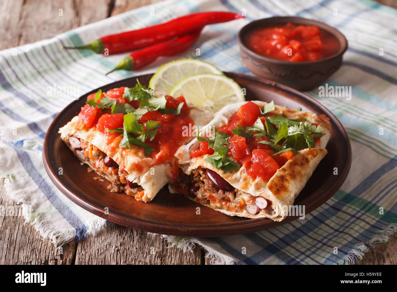 chimichanga with ground meat, beans and cheese close-up on the table. horizontal - Stock Image