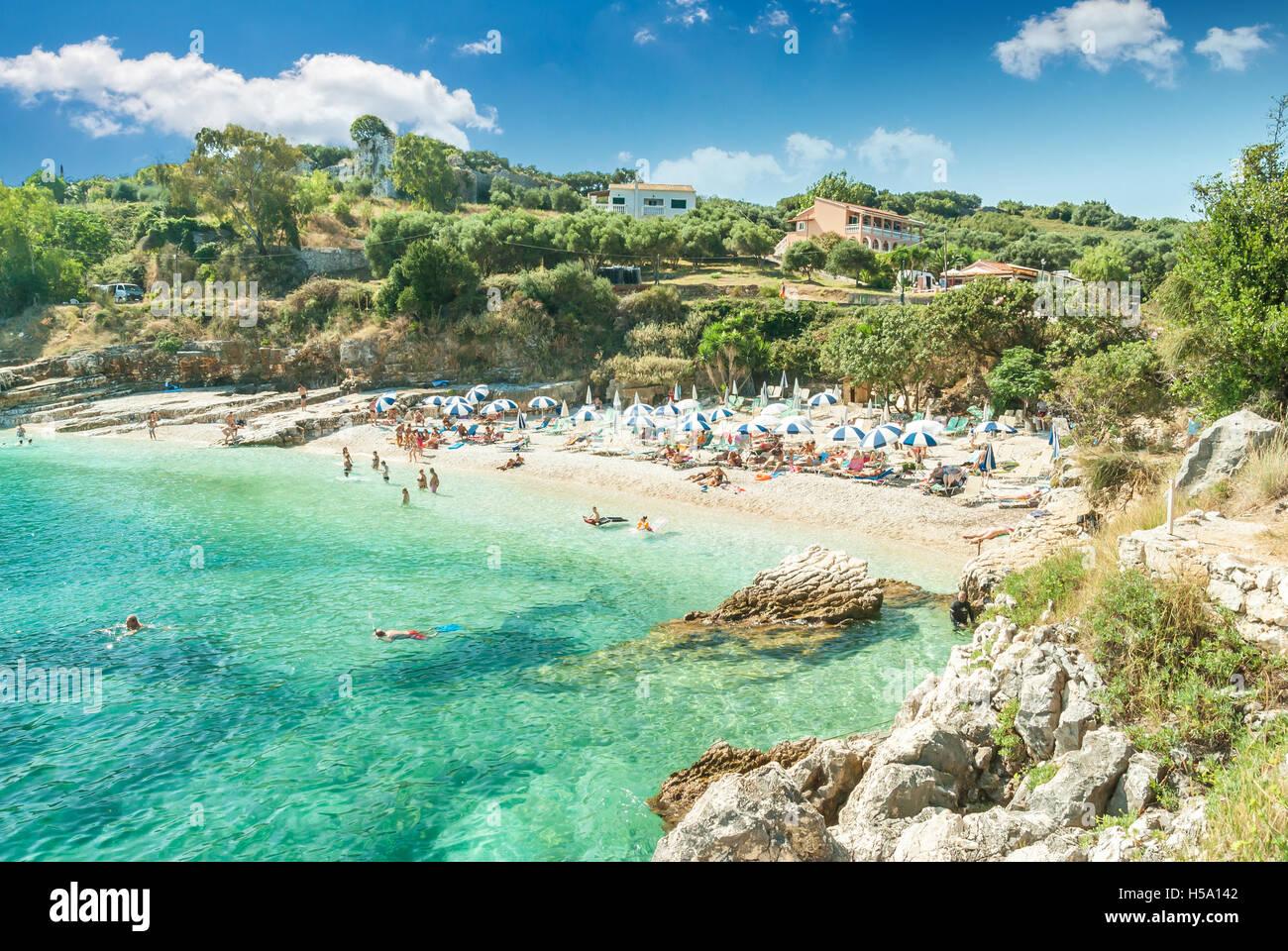 Kassiopi Beach, Corfu Island, Greece. Sunbeds and parasols (sun umbrella) on the beach. Tourists relaxing on the Stock Photo