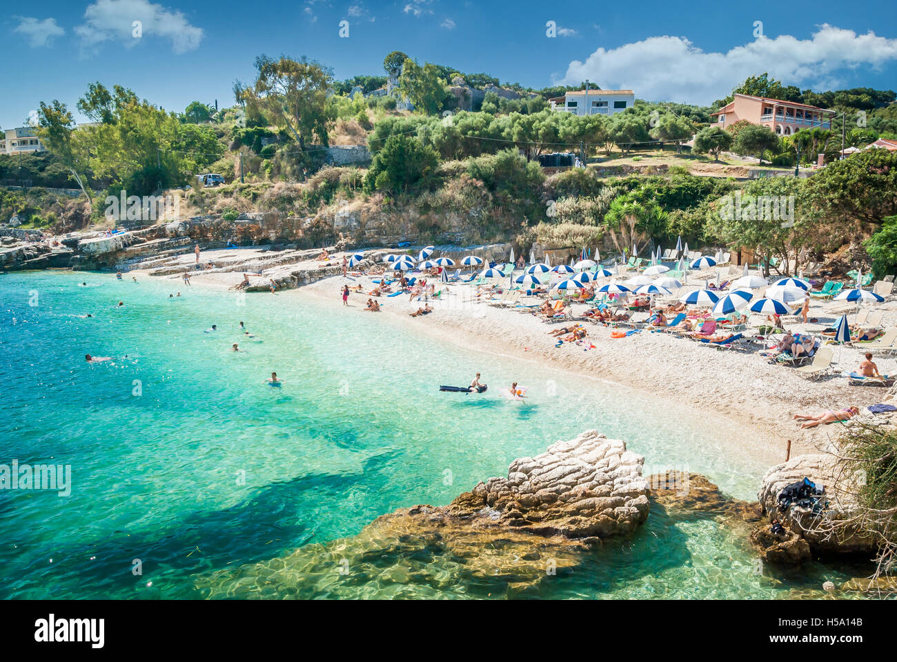 Kassiopi Beach, Corfu Island, Greece. Sunbeds and parasols (sun umbrella) on the beach. Tourists relaxing on the - Stock Image