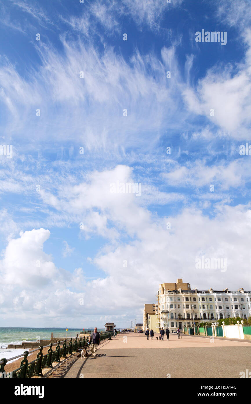 Blue sky and fair weather clouds over buildings on Brighton seafront, Brighton, East Sussex England UK - Stock Image