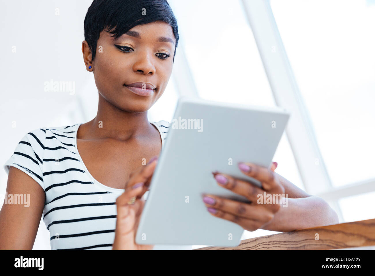 Attractive afro american businesswoman using tablet computer in office Stock Photo