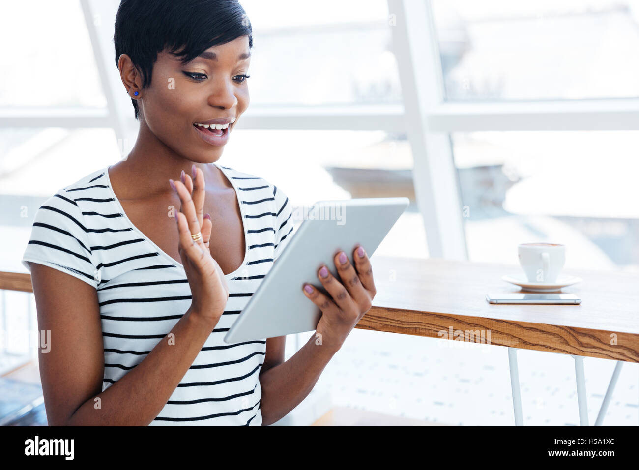 Happy afro american businesswoman holding tablet computer and waving in office - Stock Image