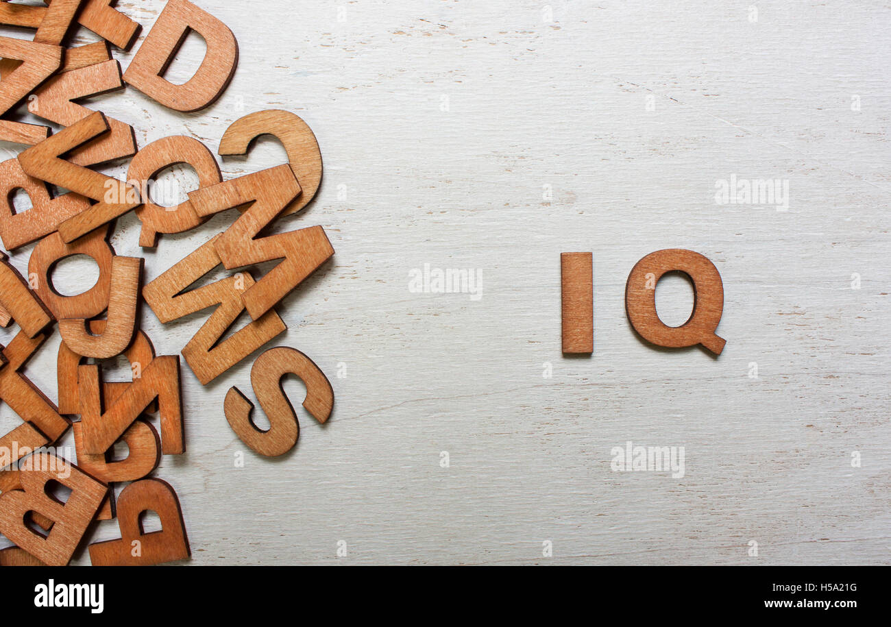 Word IQ (intelligence quotient) are made with wooden letters on an old white wooden background - Stock Image