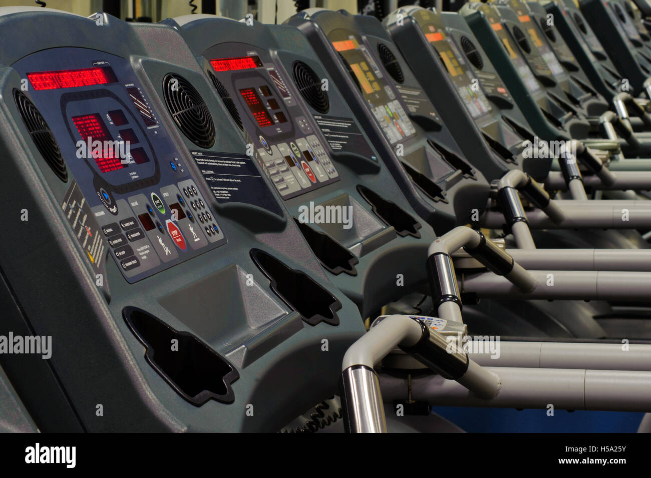 Row of treadmill consoles in the gym sitting empty. - Stock Image