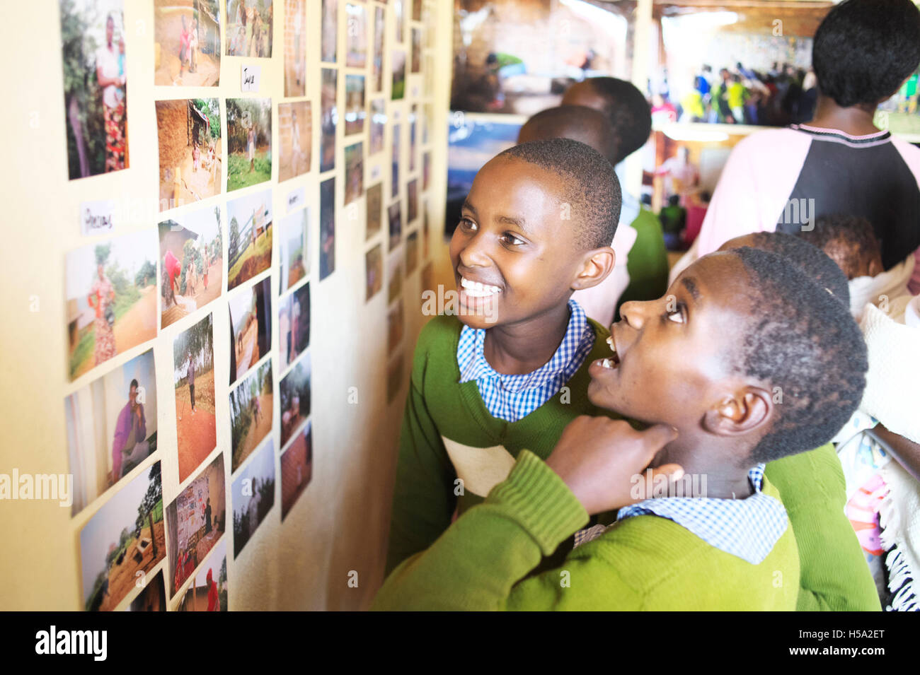 Two East African Ugandan children stare at a wall of photographs in their rural Ugandan school with happiness on Stock Photo