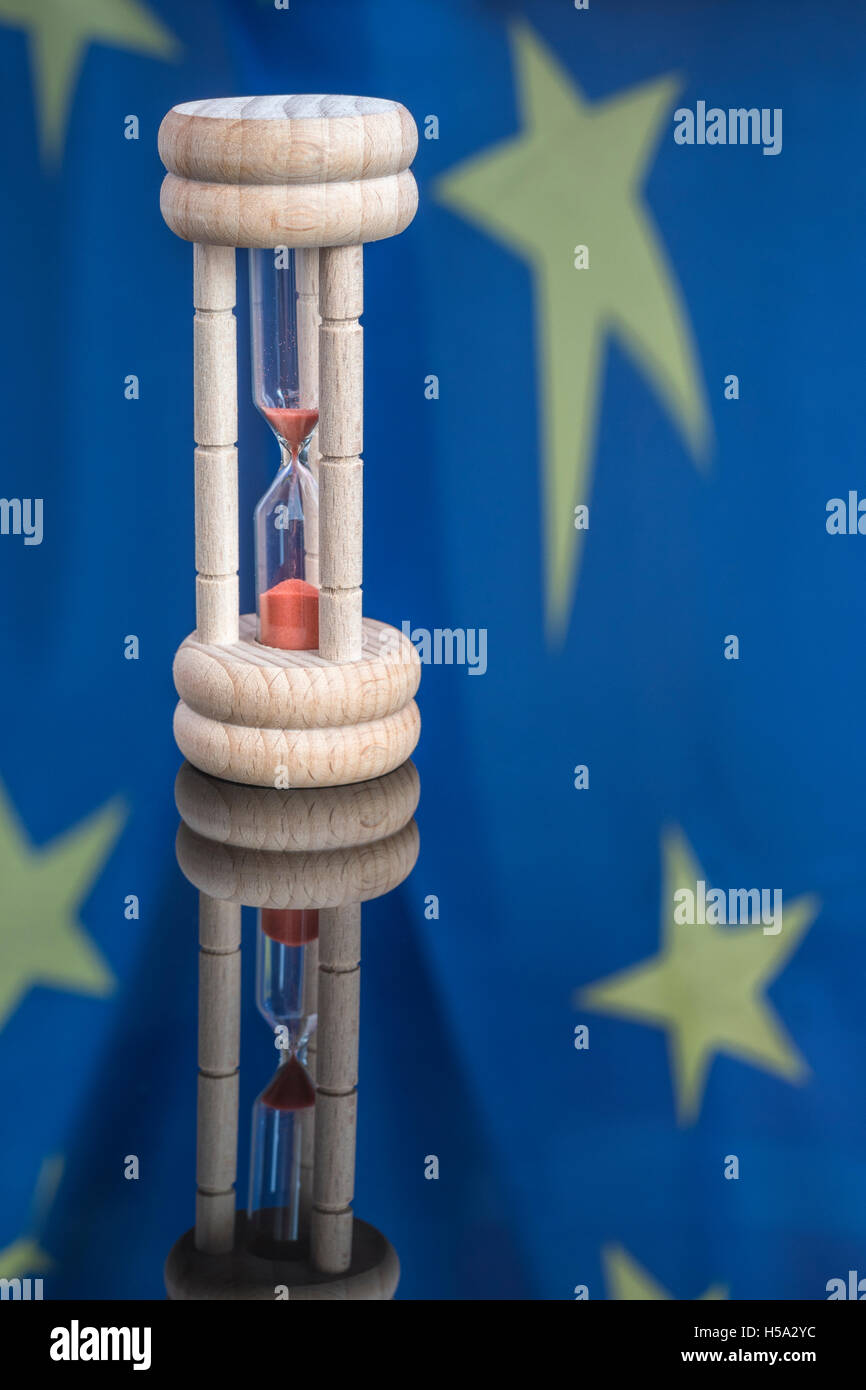 Wooden egg-timer set against reflection of EU flag as metaphor for time running out for Eurozone, Brussels, and - Stock Image
