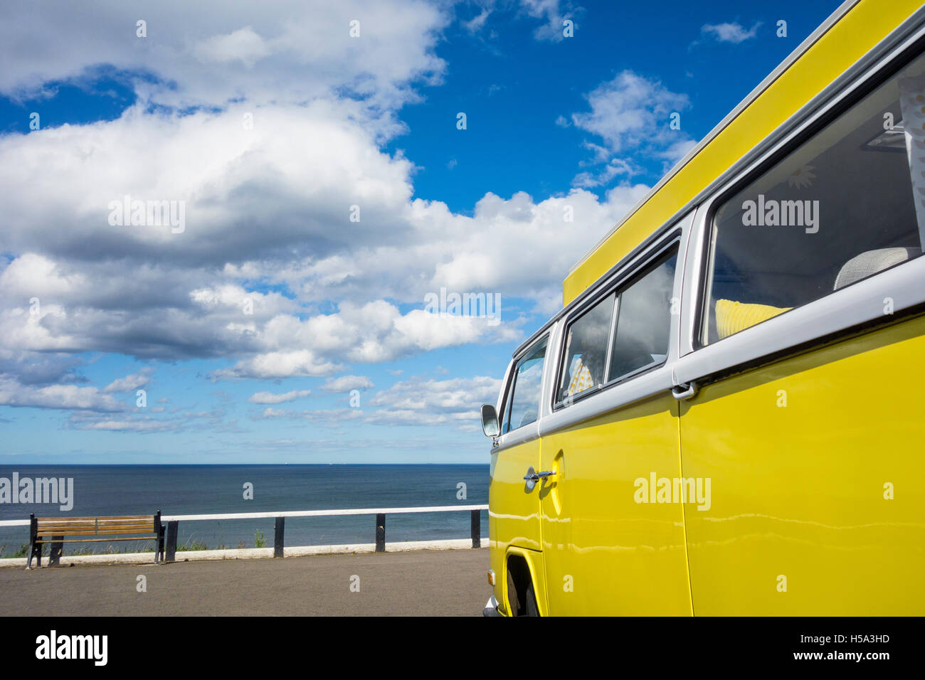 VW camper overlooking the ocean under a blue sky with cumulus clouds - Stock Image