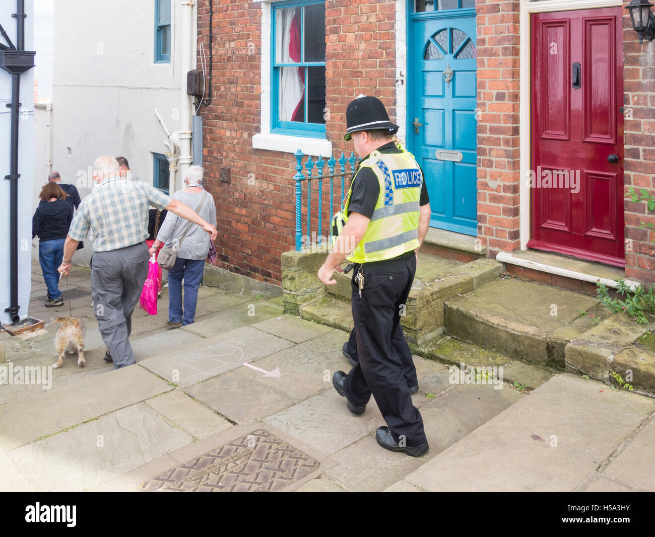 Male policeman and female police support community officer in village street in England. UK - Stock Image
